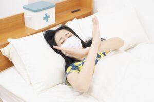 寝込んでNGポーズの病気の女性